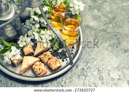 Tea glasses and pot, traditional cookies baklava. Islamic holidays decoration. Vintage style toned picture. Selective focus - stock photo