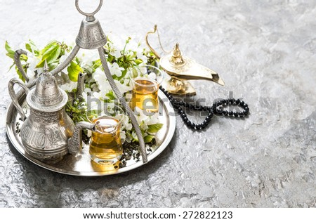 Tea glasses, oriental silver tableware, arabian lantern and rosary. Islamic holidays decoration - stock photo