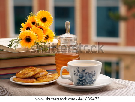Tea, honey fritters from cottage cheese, flowers and a stack of books in background windows of a building. - stock photo