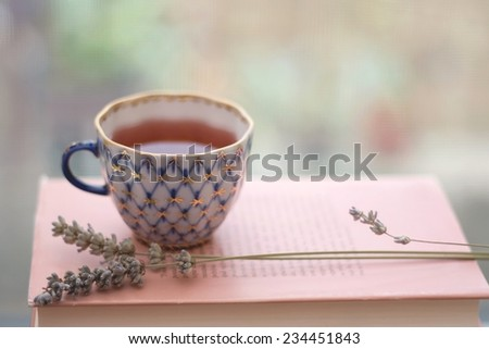 Tea in a vintage porcelain cup, with lavender and old book. Shallow depth of field and soft focus.   - stock photo