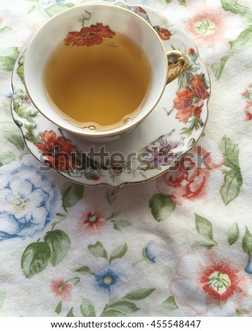Tea in cup with matching saucer on flowery print cloth - stock photo
