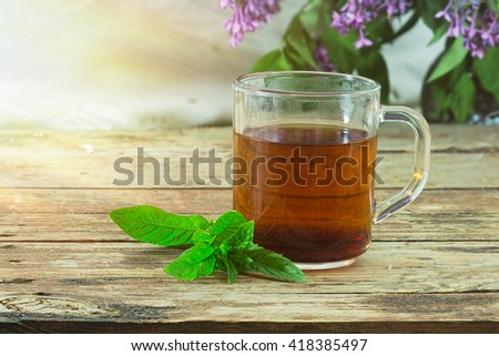 Tea in glass mug and fresh mint leaves on a rough wooden background. In the background - blurred flowers and leaves of lilac. Selective focus color image with copyspace - stock photo