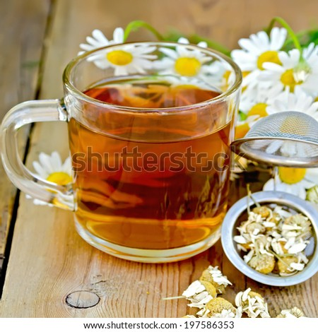 Tea in glass mug, metal sieve with dry chamomile flowers, a bouquet of fresh flowers daisies on a background of wooden boards - stock photo