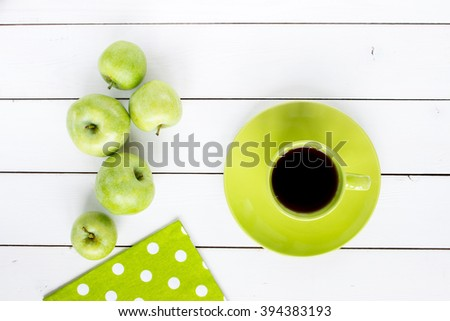 tea in green cup and ripe green apples, green napkin at white polka dots on white painted wooden table, top view - stock photo