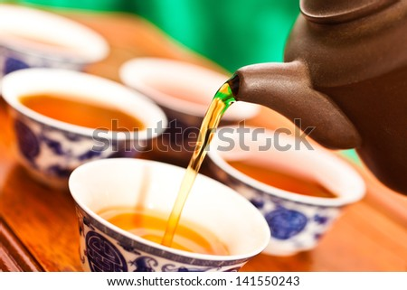 Tea is poured into the cup closeup - stock photo