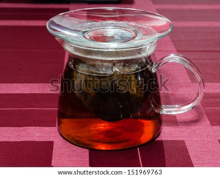 tea is ready in the glass teapot standing on a checkered cloth - stock photo