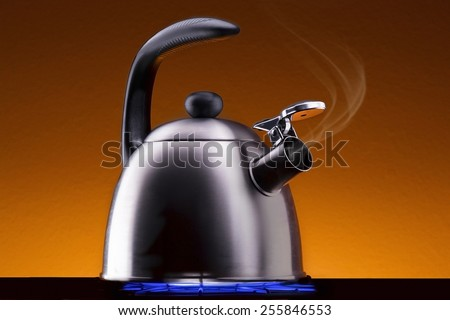 Tea Kettle with Steam Over A Hot Gas Stove - stock photo