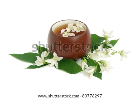 Tea leaves with fresh jasmine flowers and chinese cup on white background - stock photo