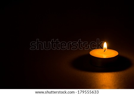 Tea light candle on black background - stock photo