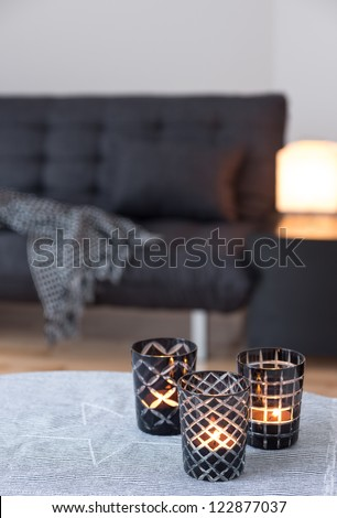 Tea-lights in glass candle holders decorating living room with gray sofa. - stock photo