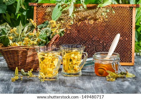Tea made of lime and honey served in summer - stock photo