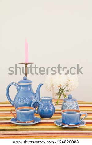 tea or coffee set on table with colorful line fabric in gray wall room - stock photo