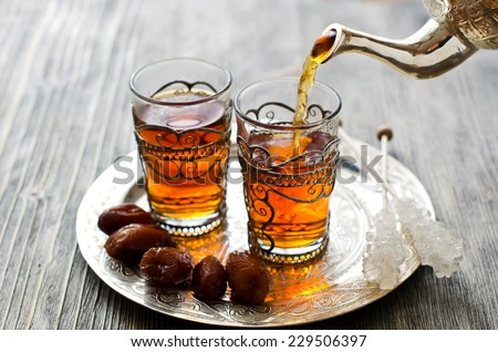 Tea pouring into glass from metal teapot - stock photo