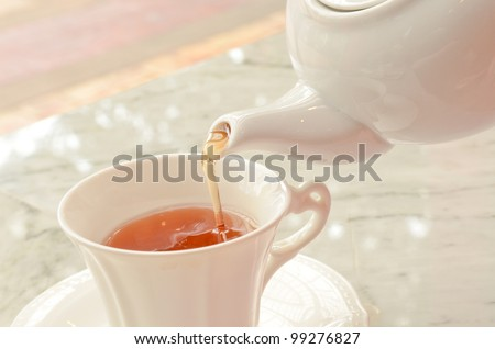 tea pouring into glass tea cup - stock photo