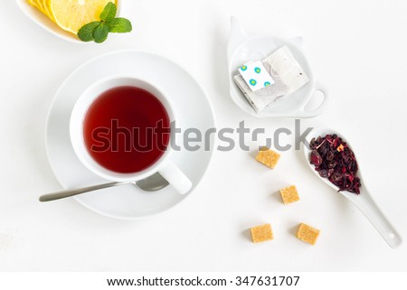 Tea set with a cup of fruit tea, lemon, filter in teapot-shaped bowl, cube sugar and tea flowers. White background, top view, minimal style. - stock photo