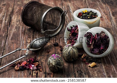 tea strainer and different varieties of tea leaves on wooden background.The toned image - stock photo