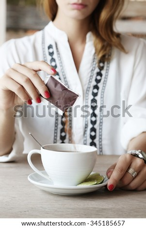 Tea time. Girl in cafe adding sugar in the cup of tea - stock photo
