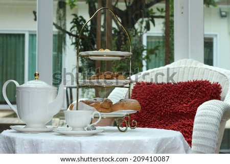 Tea time in glass house with Eclair and biscuit - stock photo