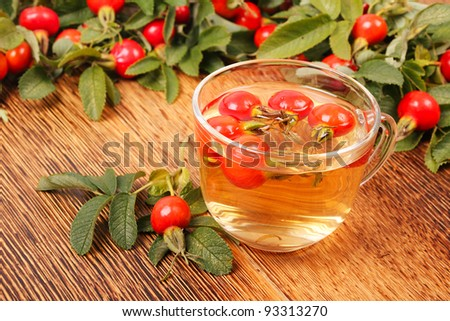 Tea with dog roses on brown wooden fence. Beautiful village background - stock photo
