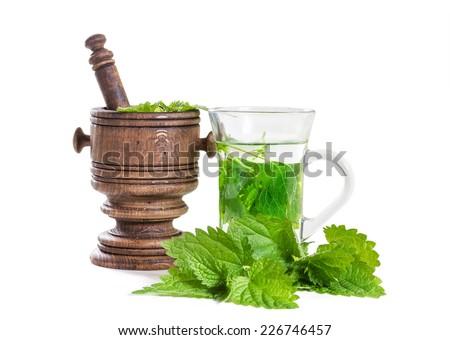 Tea with fresh nettles on white background - stock photo