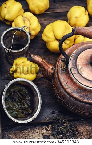 Tea with fresh quince.Wooden box with a stylish copper kettle and fruit quince - stock photo