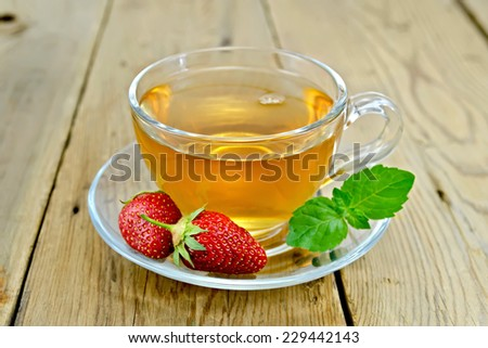 Tea with mint and strawberries in a glass cup on a wooden boards background - stock photo