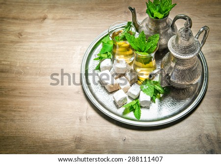 Tea with mint leaves and arabic delight. Oriental hospitality concept. Holidays table setting. Vintage style toned picture - stock photo