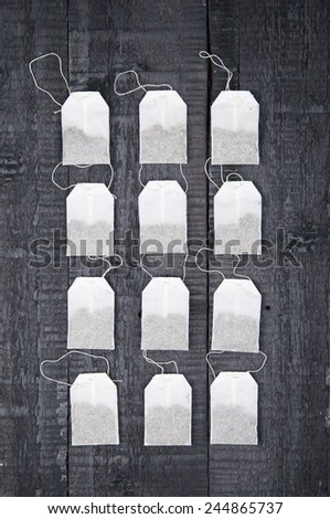 Teabags on black wooden background - stock photo