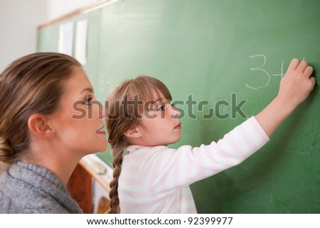 Teacher and a pupil making an addition on a blackboard - stock photo