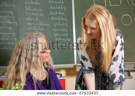 Teacher and a student in the classroom having a conversation - stock photo