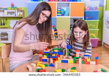 teacher and child build together toy blocks castle  - stock photo