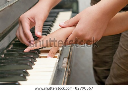 teacher and child's hands touch keyboard - stock photo