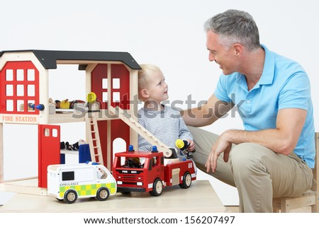 Teacher And Pupil Playing With Wooden Fire Station - stock photo