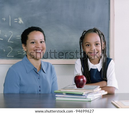Teacher and school girl smiling for the camera - stock photo