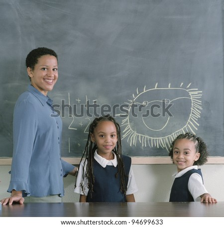 Teacher and school girls at desk - stock photo