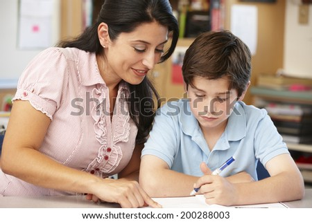 Teacher and schoolboy in class - stock photo