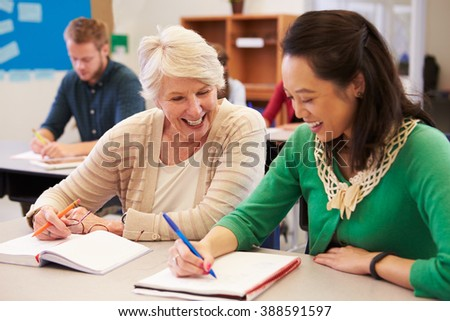Teacher and student sit together at an adult education class - stock photo