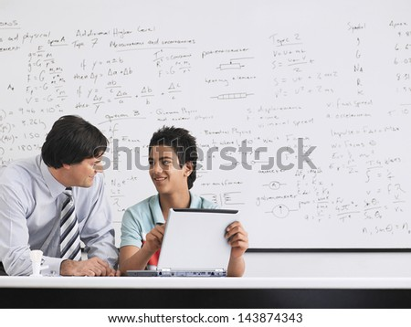 Teacher and student using laptop sitting in physics classroom - stock photo