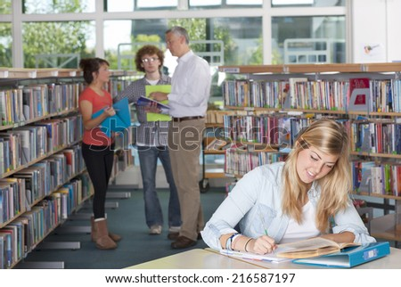 Teacher and students studying in school library - stock photo