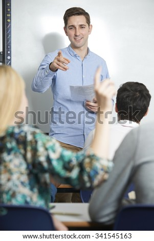 Teacher Answering Pupils Question In Classroom - stock photo