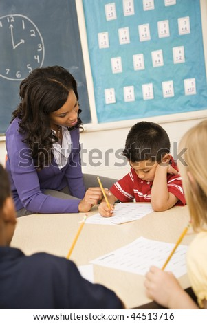 Teacher assisting young male student with lesson. Vertically framed shot. - stock photo