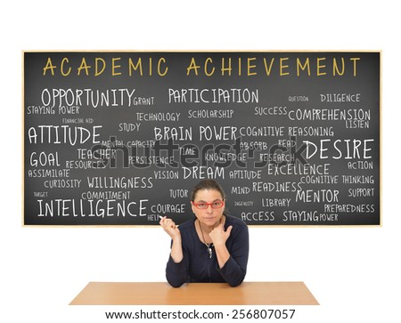 Teacher  at desk in front of Academic Achievement Blackboard: Intelligence, Readiness, Attitude, Opportunity, Preparedness, Resources, Goal, Access, Participation, Listen, Technology, Persistence - stock photo