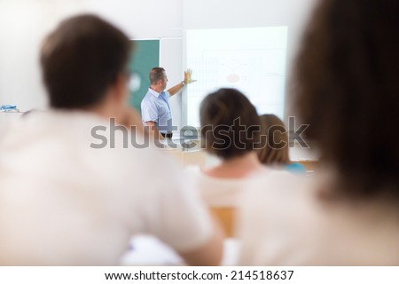 Teacher at university in front of a whiteboard screen. Students listening to lecture and making notes. - stock photo