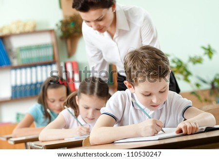 Teacher conducts the task performing by her pupils - stock photo