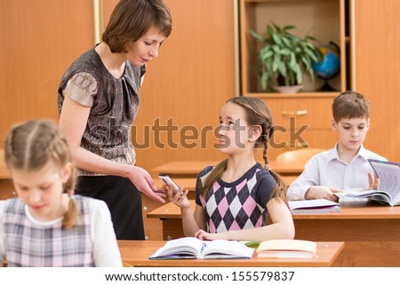 Teacher confiscating child's mobile phone at lesson in school - stock photo