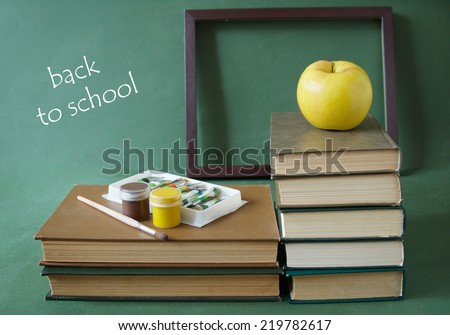 Teacher Day (still life with books, frame, paint, blackboard and apple) - stock photo