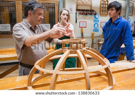 Teacher explaining a structure to two students while standing in a woodwork class - stock photo