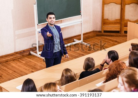 Teacher explaining something to students - stock photo