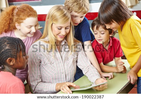 Teacher giving class with tablet computer in elementary school - stock photo