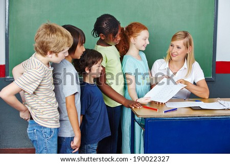 Teacher grading tests for students in elementary school at her desk - stock photo